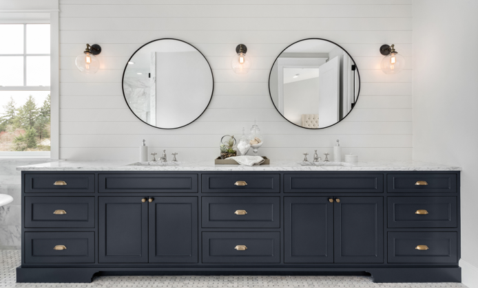 Large bathroom counter featuring white wall tile, glass ball wall lights, black cupboards, white marble countertop and matching his and hers sink and round black rimmed mirror