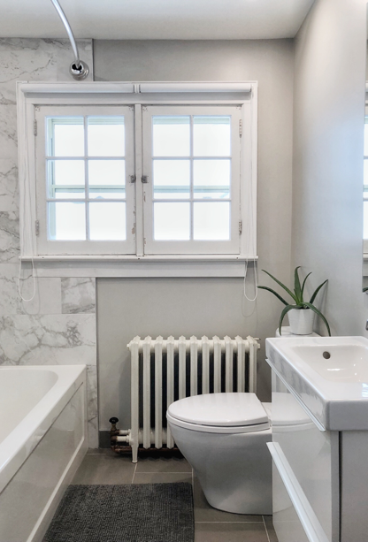 Newly renovated bathroom with grey floor tile, light grey painted walls, white and grey marble shower tiles, new compact sink and bathtub, freshly painted radiator, and vintage white window