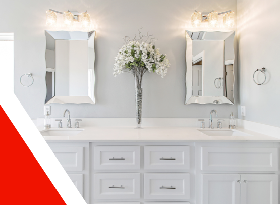 Elegant bathroom counter with white countertop and cupboards, white painted walls and matching his and hers sink, hand towel ring, wall lights and mirror