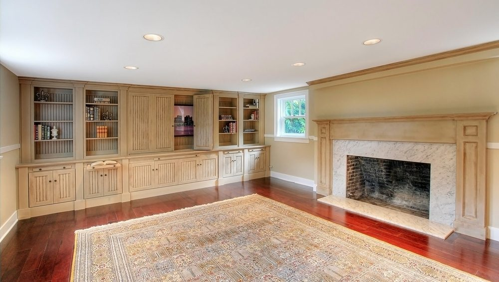 Newly remodelled basement with red hardwood floors, tan pained walls, open fireplace with white granite and natural wood mantle, and natural wood cupboards and shelves.