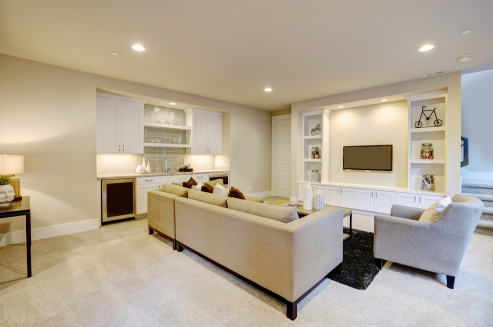 Remodeled living room with open wall shelves, beige furniure, beige carpet, white kitchenette with sink and mini fridge, and wall mounted TV.