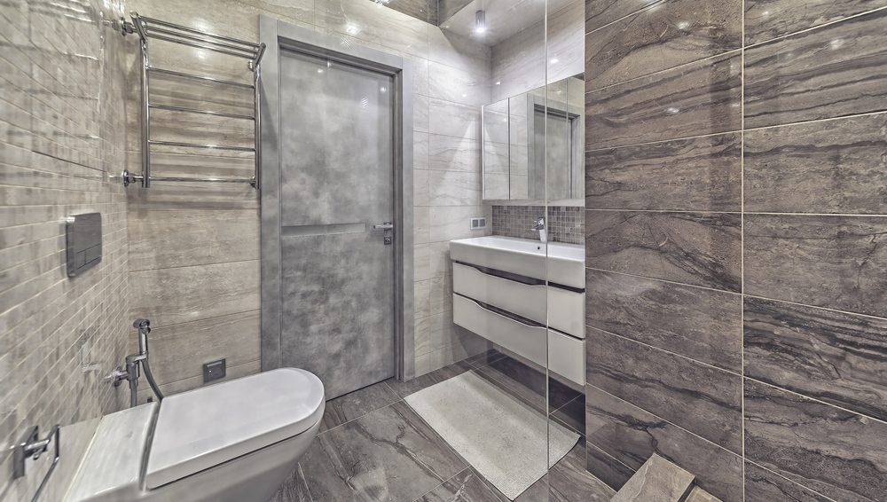 Remodeled bathroom with grey tile, modern fixtures and walk in shower